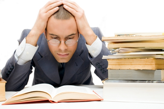 Young businessman stuck with books